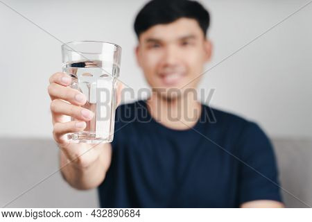 Handsome Asian Man Drinking A Glass Of Water On The Sofa At Living Room