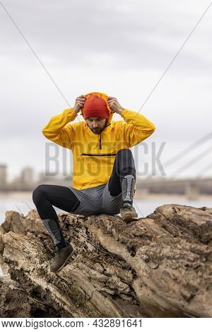 Man Sitting On A Fallen Tree Trunk, Taking A Break While Jogging By The River On An Overcast Autumn