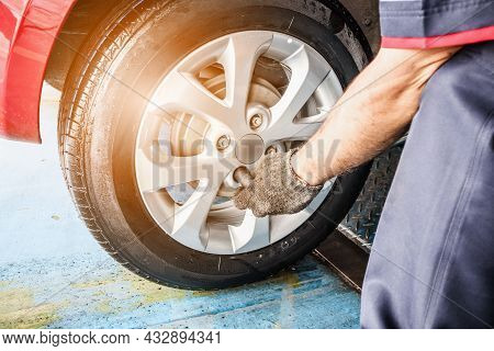 Tire Replacement Service, Mechanic With Wrench Working At Auto Repair Shop Changing Car Wheel