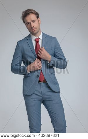 sexy businessman arranging his suit and posing with attitude on gray background