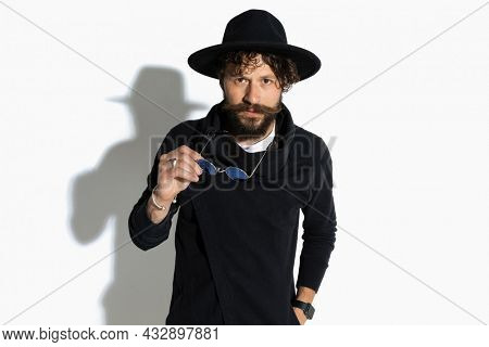 cool fashion model removing his sunglasses, holding one hand in pocket and posing with attitude