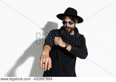 cool casual man pulling his sleeve with attitude and wearing sunglasses on white background