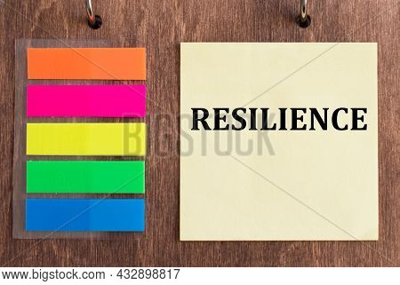 Resilience On Crumpled Yellow Paper On Wooden Background
