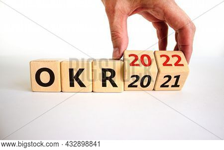 Okr, Objectives And Key Results Symbol. Businessman Turns Cubes With Words 'okr 2021' And 'okr 2022'