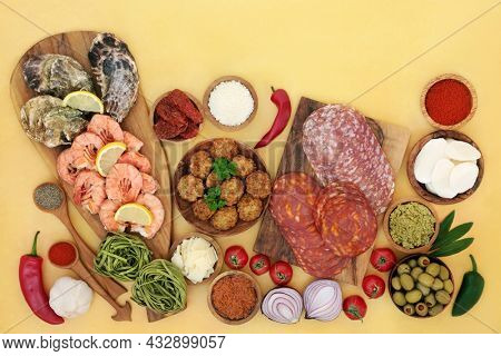 Healthy food for Italian Mediterranean diet concept with meat, vegetable seafood. High in antioxidants, anthocyanins, fibre, lycopene, omega 3 and protein. Flat lay on mottled yellow.