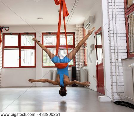 Young Slim Woman Wrapped In Hammock Suspension Hanging Upside Down While Doing Aerial Yoga, Upside D