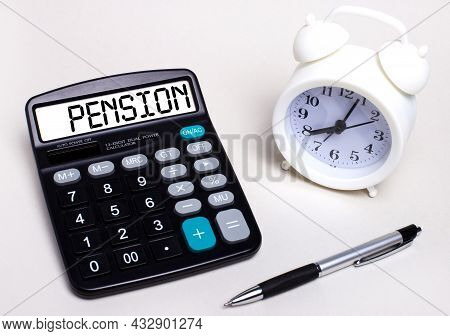On The Light Table There Is A Black Calculator With The Text Pension On The Scoreboard, A Pen And A