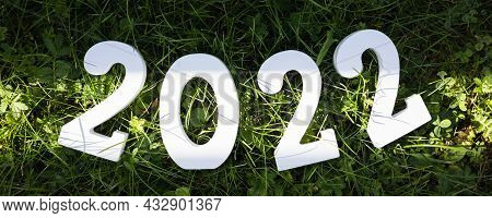 Happy New Year 2022. White Wooden Number 2022 On Green Grass. Banner.