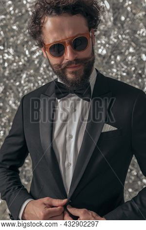 cool elegant groom in black tuxedo arranging jacket and looking to side while posing on tinfoil background in studio