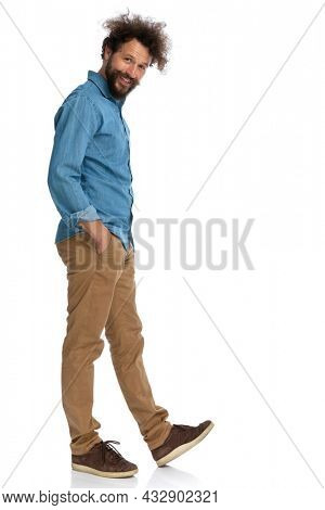 side view of a casual man stepping to the side and holding hands in pockets on white background