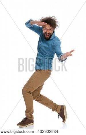 side view of a casual man messing around and walking to the side on white background