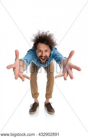 young casual man leaning forward and greeting someone with open arms on white background