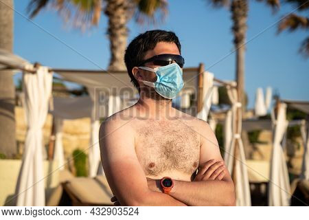 Resting Man In A Protective Mask On A Dirty Beach Alone Against The Background Of Palm Trees And Sun