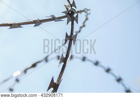 Barbed Wire Spiral Through Which The Blue Sky Is Visible