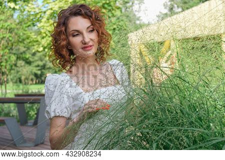 Attractive Curly-haired Woman In A White Dress Examines Ornamental Plants In Her Garden. Landscape D