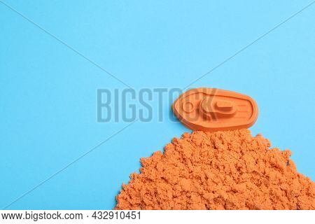 Orange Kinetic Sand On Light Blue Background, Flat Lay. Space For Text