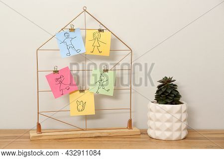 Pictures Of Family Members Attached To Decorative House Near Plant On Wooden Table