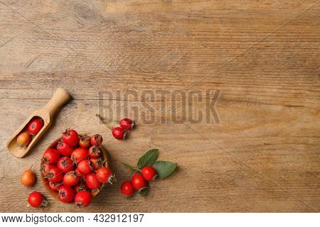 Ripe Rose Hip Berries With Green Leaves And Scoop On Wooden Table, Flat Lay. Space For Text