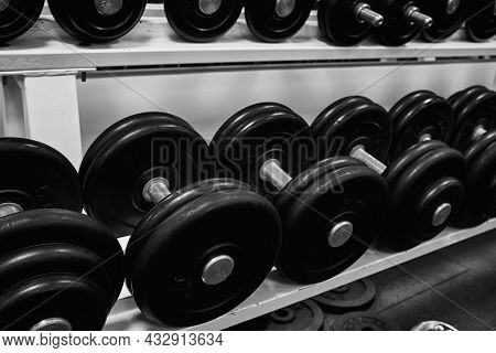 Dumbbells In The Gym. Sports Dumbbells In In A Rack In Sports Club. Black And White Photo