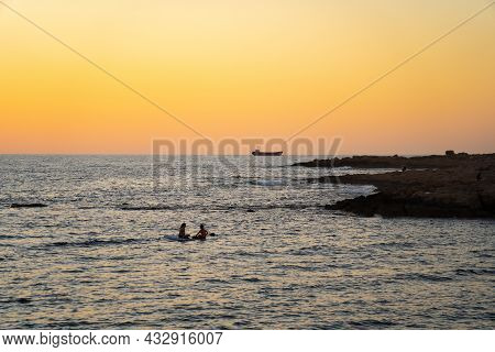 Two Women Sharing Paddle Board At Sunset On Calm Waters In Mediterranean Sea In Cyprus. Two Girls On