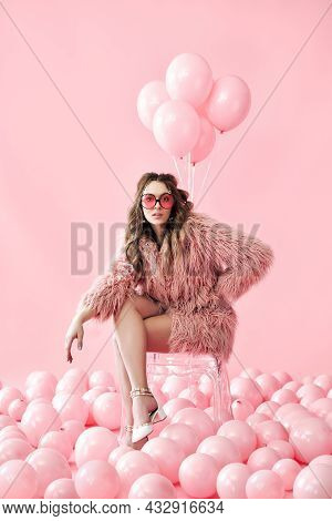 Confident Fashion Woman Sitting On Chair Posing On Many Pink Balloons Background