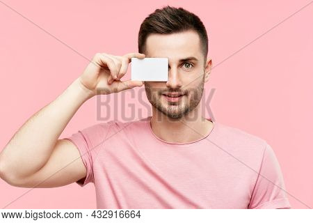 Handsome Smiling Man Holding Credit Card Near His Face Closing Eye Over Pink Background