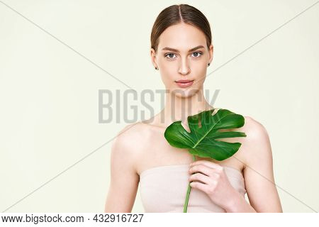 Young Beautiful Woman Holding Monstera Tropical Leaf With Copy Space