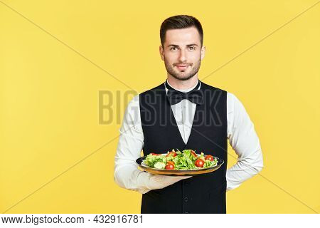 Happy Smiling Waiter Holding Plate With Healthy Vegetable Salad Ready To Serve