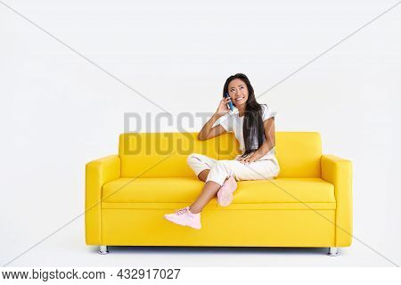 Smiling Asian Woman Talking On Cell Phone Sitting On Yellow Couch
