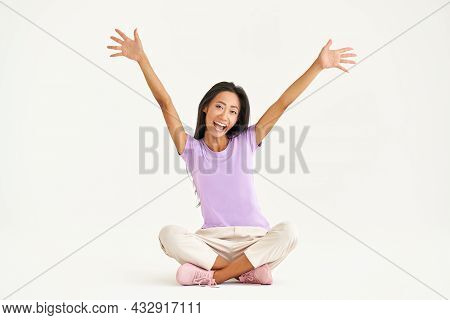 Smiling Young Asian Woman Raised Arms Up Screaming And Celebrating While Sitting Sitting On Floor