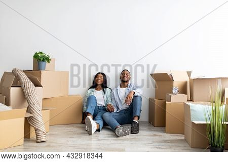 Happy Millennial African American Spouses Relocating To New Apartment, Sitting Among Cardboard Boxes