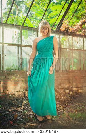 Young Woman With Bob Haircut In Turquoise Evening Dress On One Shoulder Is Standing In An Abandoned