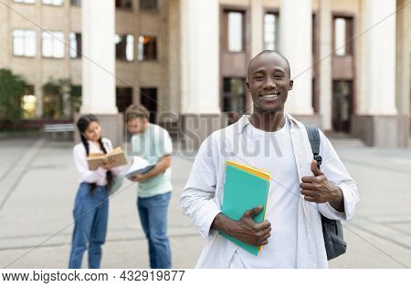 Happy African American Student Guy Standing Outdoors With Classmates In University Campus, Posing An
