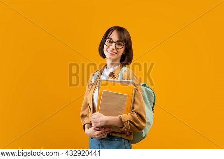 Academic Education. Young Lady With Backpack And Notebooks Smiling At Camera Over Yellow Studio Back