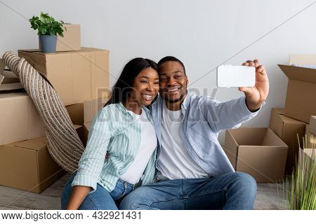 Relocation And Ownership Concept. Happy Young Black Couple Making Selfie After Moving To Own House
