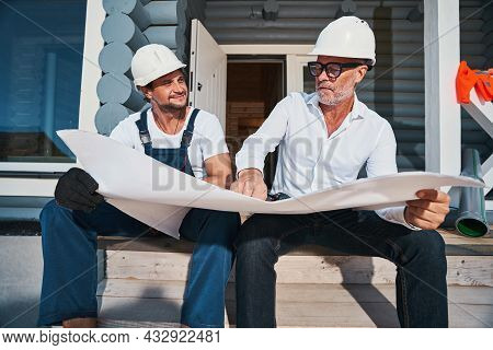 Builders Sitting On Porch Stairs And Discussing Construction Plans