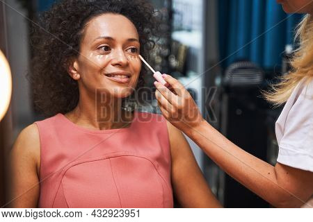 Positive Delighted Curly Haired Woman Doing Makeup