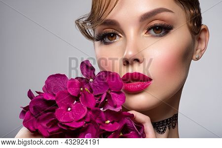 Beautiful white girl with purple flowers. Stunning brunette girl with big violet bouquet flowers. Closeup face of young beautiful woman with a healthy clean skin. Pretty woman with bright makeup