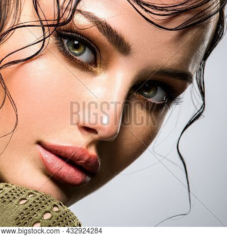 Beautiful  woman Face with a bang. Model looking at camera. Sexy woman looks at camera. Closeup portrait of a beautiful young fashion woman with glamour makeup