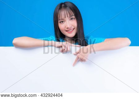 Beautiful Asian Young Woman With Bangs Hair Style In Blue T Shirt Smiling And Pointing Finger A Blan