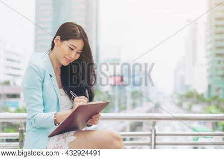 Business Asian Woman Employee Sits Down And Writes Down The Paperwork She Has Prepared To Work Outsi