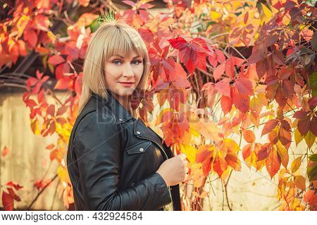 Portret Of Young Woman With Bob Haircut In A Black Leather Jacket Is Standing In An Abandoned Greenh