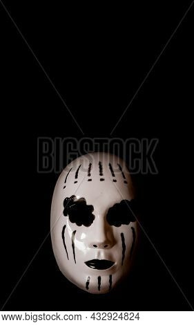 Scary White Mask Of A Mystery Female On Black Background With High Contrast. Costume For Halloween O