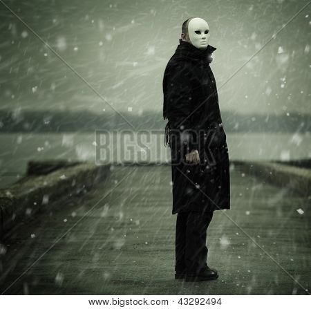 man with white mask near the river and snow