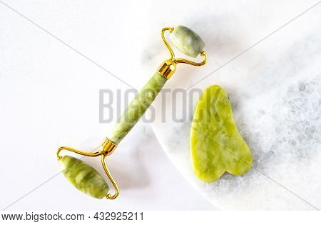 Green Face Roller And Gua Sha Massager Made From Natural Jade Nephritis Stone Over Marble Background