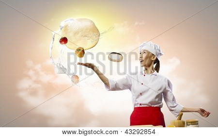 Asian female cook making pizza standing against color background poster