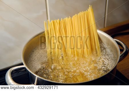 Preparing Spaghetti In Boiling Water In Cooking Pot On Stove