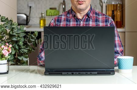 Trendy Mature Man Working From Home With Laptop Sitting At The Table In His Kitchen, Dressed In Shir