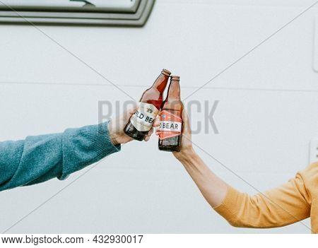 Hands clinking bottle of beers