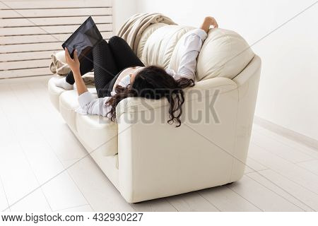Latin Pregnant Woman Using Tablet Computer While Lying On Sofa At Home. Pregnancy And Information Fo